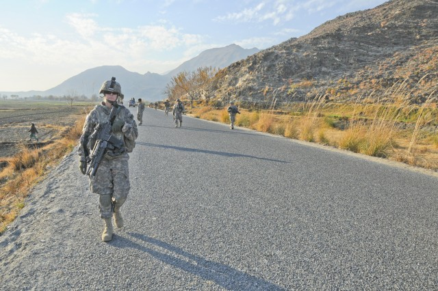 Spc. Christine Gallagher, machine-launched grenade gunner with the 64th Military Police Company, based at Combat Outpost Fortress, Afghanistan, conducts a foot patrol through Noor Gal district, Jan. 3.