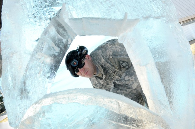 Spc. William Fadden, Fort Sill (Okla.) Culinary Team, is framed through a giant piece of ice as he cuts into it using a chainsaw.