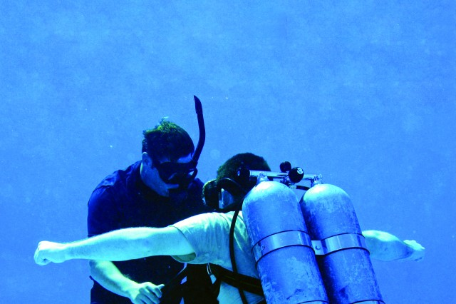 A Combat Diver Qualification Course instructor inspects a student's equipment during open-circuit training in the pool.