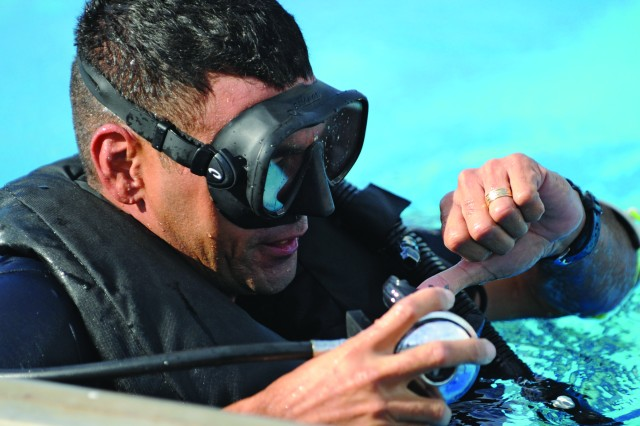 Sgt. Eddy Rojas, Combat Diver Qualification Course instructor, adjusts his breathing apparatus in between pool training sessions.