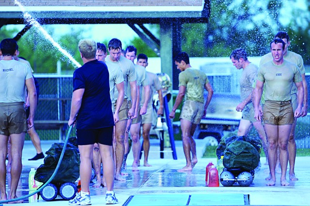 Combat Diver Qualification Course students rush to formation, while cadre prepare them for training in the pool, October 2010.