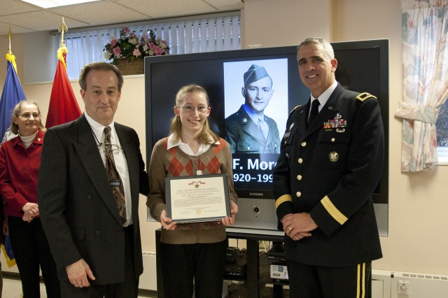 Lora Morgan, center, poses with the posthumous Bronze Star citation for her grandfather, pictured in the background. To Lora's right is her father, Richard Morgan, and to her left, Picatinny Arsenal Senior Commander Brig. Gen. Jonathan A. Maddux.