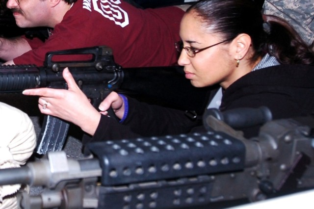 FORT HOOD, Texas - Tina Flores-Nevarez, a human resource generalist for Texas A&M University - Central Texas engages simulated targets with weapon simulators at the Warrior Skills Trainer, Fort Hood March 4.