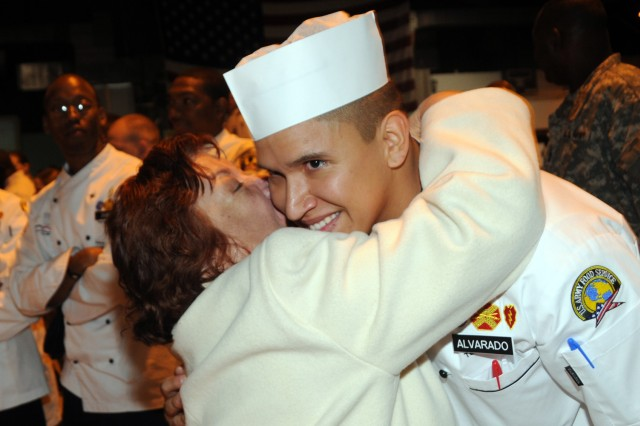 Spc. Oscar Alvardo, stationed out of Wheeler Army Airfield, Hawaii, hugs his grandmother after winning a gold medal for the Hawaii team in the junior chef of the year competition that was part of the 36th Annual Culinary Arts Competition, March 3-9, at Fort Lee, Va.