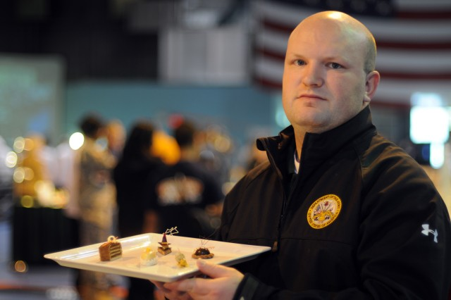 """Staff Sgt. Michael Bogle, assigned to the Army Executive Dining Facility at the Pentagon, earned a silver medal for his contribution to his team's table during the 36th Annual Culinary Arts Competition, March 3-9, at Fort Lee, Va.  His platter featured five tiny dessert items -- small cakes and pastries -- all under the team's """"farm to table"""" theme. Some items took five hours to make."""