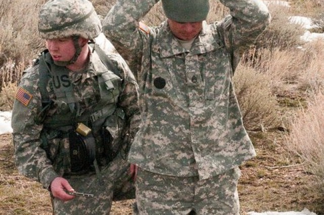 Pfc. Jared Campbell of the 786th Quartermaster Company removes weapons from a detainee during the Warrior Tasks portion of the Best Warrior competition at Camp Williams, Utah, March 5, 2011. Army photo by Spc. Aloree Amodt, 358th Public Affairs Detachment.