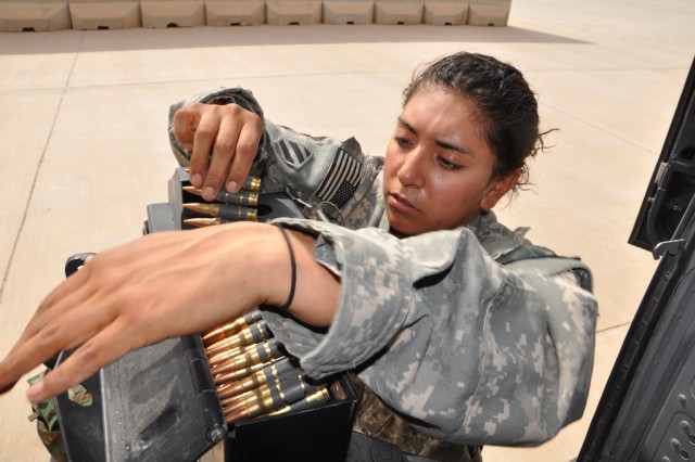 Spc. Crisma Albarran detaches an ammunition case from its mount after a UH-60 Black Hawk helicopter flight over Iraq, March 14, 2010. Albarran with Task Force 38's B Company, 3rd Battalion, 158th Aviation Regiment, volunteered for the job as door gunner prior to her second deployment to Iraq, and has flown more than 100 hours toward her door gunner certification. During her first Iraqi deployment in 2007 she was a petroleum supply specialist with the 3rd Infantry Division.