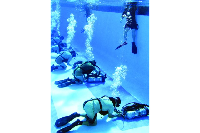 Instructors observe Combat Diver Qualification Course students during open-circuit training in the pool, which prepares them for the more advanced closed-circuit apparatus that is most often used by combat divers.