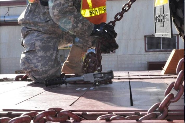 Pfc. Luis Delgado, a 551st Inland Cargo Transfer Company truck driver, sets chains in place during rail-loading operations at the rail yard Camp Carroll, South Korea Mar. 3, 2011. The chains will be used to hold vehicles in place on the rail cars during their transportation to the northern part of South Korea.