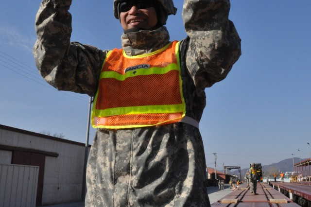 Spc. Jonhthan Garcia, a 551st Inland Cargo Transfer Company truck driver, guides a vehicle onto a rail car at Camp Carroll, South Korea Mar. 3, 2011. The 551st ICTC helped incoming units upload their vehicles during rail-loading operations as part of Exercise Foal Eagle 2011.