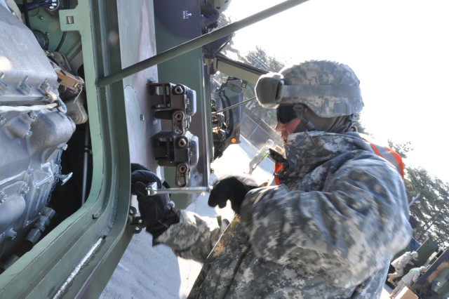 Spc. Matthew Miller, a driver with 2nd Battalion, 146th Field Artillery, removes the bolts from an engine compartment panel on a M-1068 Fire Direction Control Tank Mar. 2, 2011. The 2nd Bn., 146th FA conducted pre-driving preventative maintenance checks and services to their vehicles after receiving them from Army Prepositioned Stock 4 yard on Camp Carroll, South Korea.