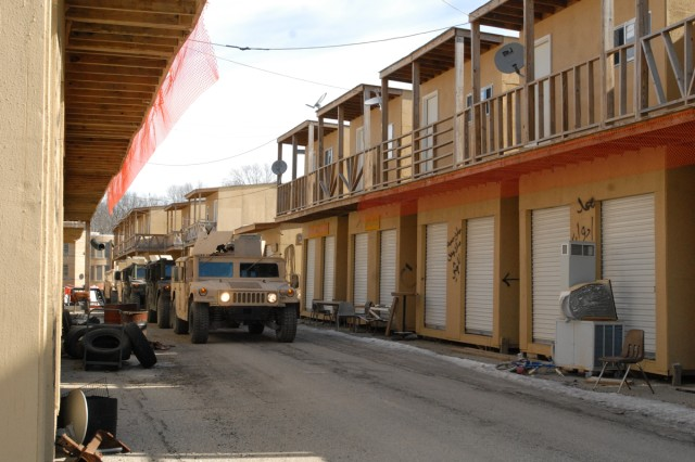 A convoy moves down a mock alleyway at Muscatatuck Urban Training Center, Ind., Feb. 10, 2011. Instructors strive to make the scenery as authentic as possible for students attending the Civilian Expeditionary Workforce pre-deployment training course at Muscatatuck and nearby Camp Atterbury.