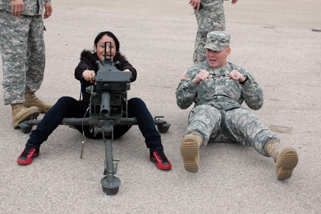 FORT HOOD, Texas-Sgt. Bret Lowery (right), a native of Springfield, Idaho, a multiple launch rocket system gunner for Battery C, 2nd Battalion, 20th Field Artillery Regiment, 41st Fires Brigade, demonstrates to Viviana Vaquera, a senior at A.J. Moore Academy, how to properly operate the MK19 grenade launcher March 4.