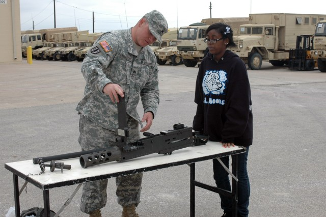FORT HOOD, Texas-Sgt. David Summers, from Emmett, Idaho, a multiple launch rocket system crew chief for Battery B, 2nd Battalion, 20th Field Artillery Regiment, 41st Fires Brigade, takes apart the .50 caliber machine gun to show Kennedy Haynes, a freshman at A.J. Moore Academy, how to load and maintain the weapon March 4.