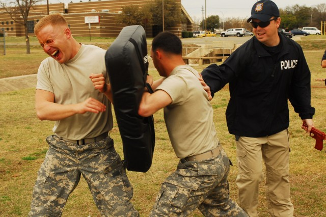 FORT HOOD, Texas - Spc. Zachary Isaac (left), a military policeman with Headquarters and Headquarters Company, 2nd Brigade Combat Team, 1st Cavalry Division, attacks a bag after being sprayed with pepper spray during a training course on Fort Hood, Texas, March 4.