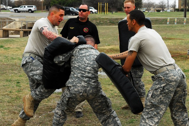 FORT HOOD, Texas - Sgt. Raymond Adams (left), a military policeman with Headquarters and Headquarters Company, 2nd Brigade Combat Team, 1st Cavalry Division, performs knee strikes on a bag after being sprayed with pepper spray March 4.