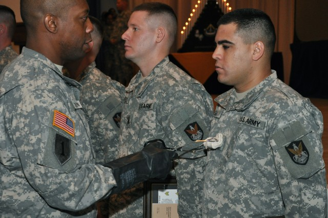 """Headquarters and Headquarters Company, 1st Space Battalion, 1st Sgt. Marcus Calhoun uses """"rocket fuel"""" to wash the newly-earned sergeant stripes of Sgt. William Bassat. The 22 new noncommissioned officers had their new rank washed with several symbolic substances, including the blood of fallen comrades and sweat from Kevlar, during the NCO induction ceremony hosted by the 1st Space Battalion."""