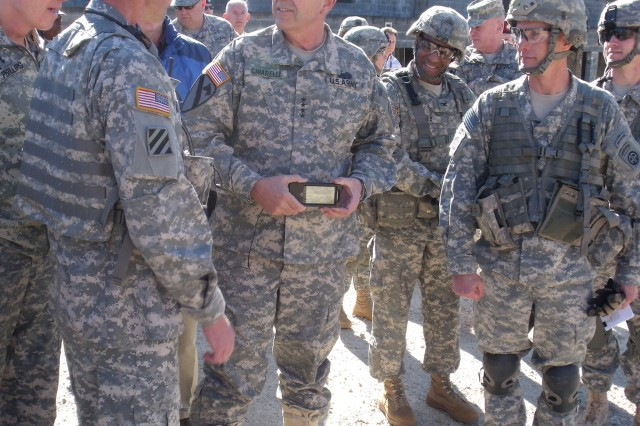 Gen. Peter Chiarelli, the ArmyAca,!a,,cs vice chief of staff, holds a prototype handheld with applications to track friendly forces and exchange photos.