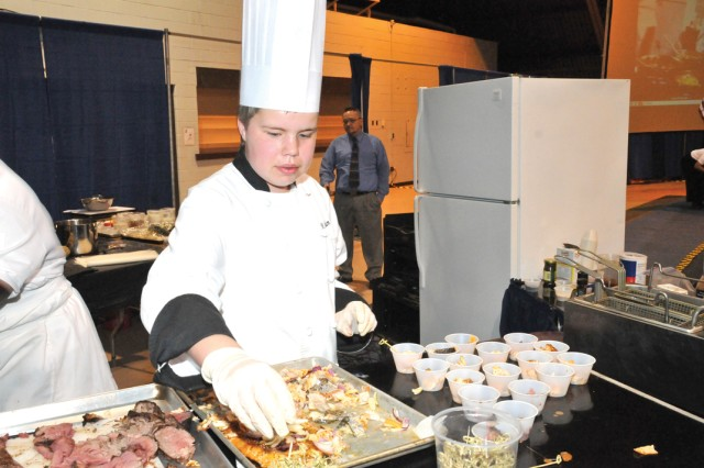 Adam Eudy serves a salmon dish to visitors at the 36th Annual Culinary Arts Competition Saturday.