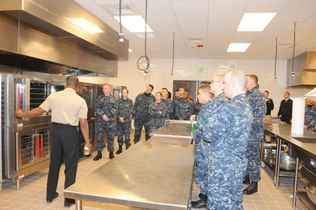 """Navy Culinary Specialist 2nd Class Juan Carethers, Navy Culinary Specialist """"A"""" School instructor, shows new Sailors around a galley that was especially design to mimic ships and submarines. Both the Air Force and the Navy took special care to ensure their new culinary training areas would be similar to what the Airmen and Sailors would see out in the operational force."""