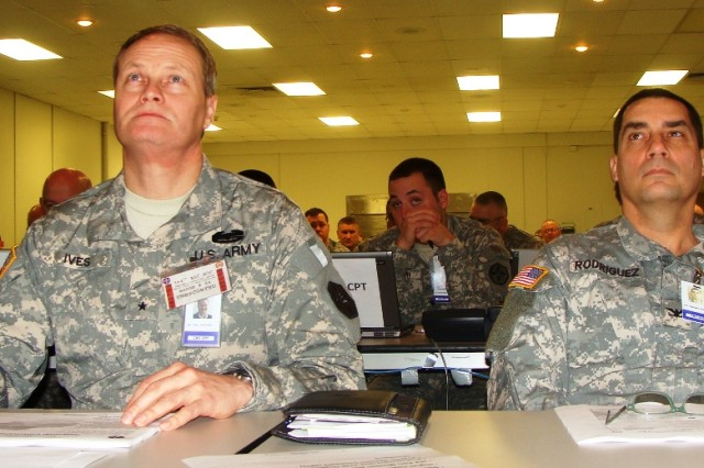 Brig. Gen. Jonathan G. Ives, left, commanding general of the 364th Expeditionary Sustainment Command, and Col. Ruben Rodriguez, deputy commanding officer, listen to a support operations briefing during the unit's joint operations center exercise (JOCEX). Army photo by Spc. Christopher A. Bigelow, 364th ESC public affairs.