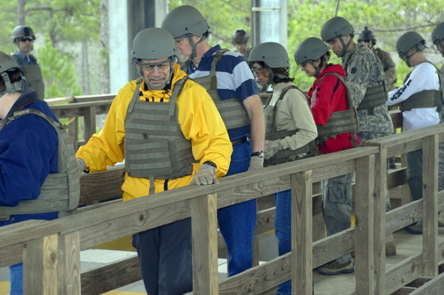 Wearing body armor and helmets on the catwalk above, National War College students watch a team of Rangers enter the shoot house Friday at Booker Range as part of a 75th Ranger Regiment demonstration.