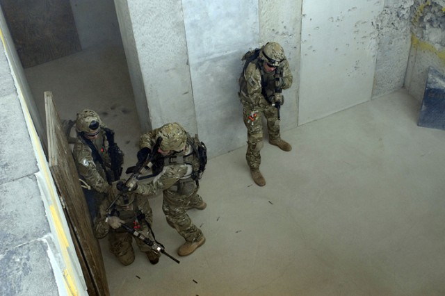 "The Rangers burst through a door while ""clearing"" a room Friday in the shoot house at Booker Range."