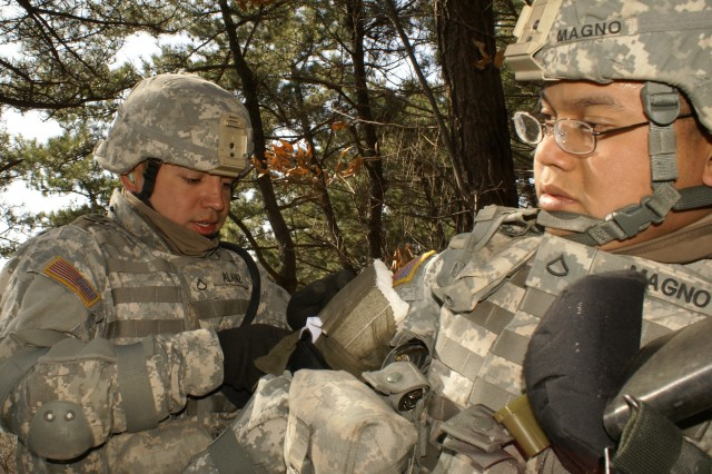 Pfc. Robert Alaniz (left), a 551st Inland Cargo Transfer Company truck driver, applies a dressing and tourniquet to Pfc. Mark Magno (right), a 551st Inland Cargo Transfer Company truck driver, during training at Busan, South Korea in support of Exercise Foal Eagle 2011 Mar. 7, 2011.