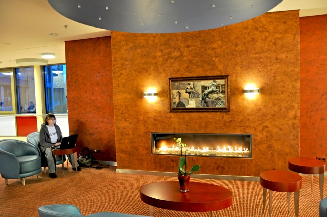 A Wiesbaden Army Lodge patron enjoys Internet access and the fireplace ambience in the lobby area.