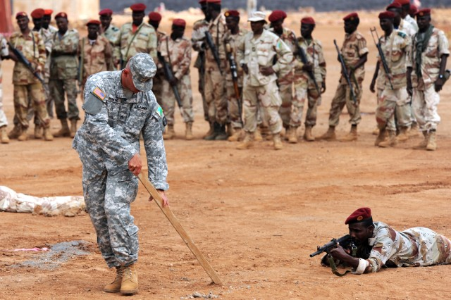 U.S. Army Staff Sgt. Nelson Perkins draws lines in the dirt to show a soldier of the Djiboutian Army's 1st Quick Reaction Regiment his sector of fire during a training scenario at Camp Ali Oune, Djibouti, Feb. 2, 2011.