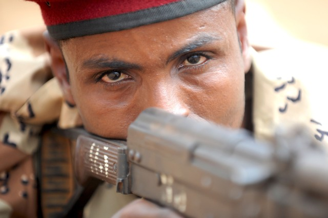 Djiboutian Army 2nd Company 1st Rapid Action Regiment, Sgt. Abeh Abdallah, squad leader, aims his weapon during a contact drills practical application during infantry skills training in Ali Oune, Djibouti, Feb 2, 2011.