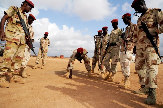 Djiboutian Army 1st Rapid Action Regiment Squad Leader, Abou Bakr Housein, draws a sand table for his fellow squad members during a break from instruction on basic infantry movements, as part of a training course held in Ali Oune, Djibouti, Feb 2, 2011.