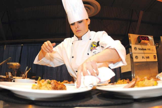 Pfc. Yulia Gonzalez of the Fort Sill Culinary Team, wipes off plates prior to presenting her work to judges Friday during the Practical and Contemporary Hot Cooking event Friday at the Post Field House. 