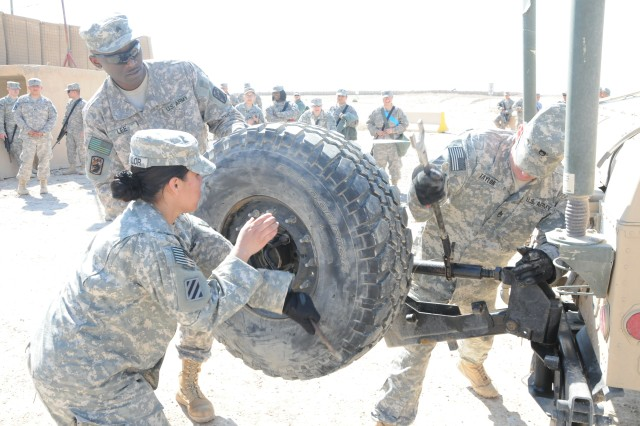 Three members of Alpha Team for the Special Troops Battalion, 3rd Sustainment Brigade, 103rd Sustainment Command (Expeditionary), race to remove the spare tire off the back of a Humvee, during the Humvee tire exchange event for the Provider Challenge Feb. 19 at Contingency Operating Base Speicher, Iraq.