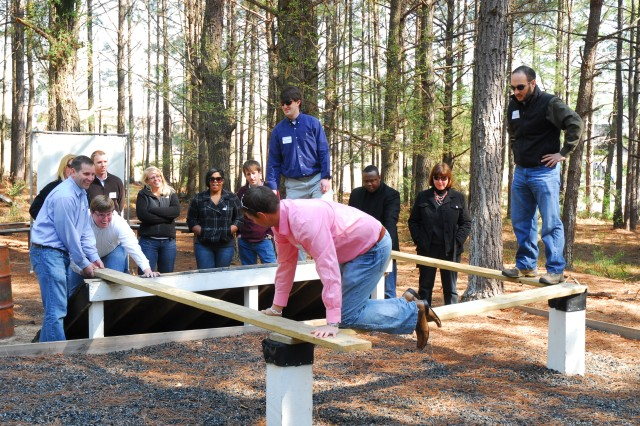 Leadership Columbia participants, clockwise, Anthony Hernandez, Charles Appleby, Nathan Arnold and Brian Pattison try the teamwork approach to solving the Destroyed Bridge obstacle Tuesday at the Teamwork Development Course.