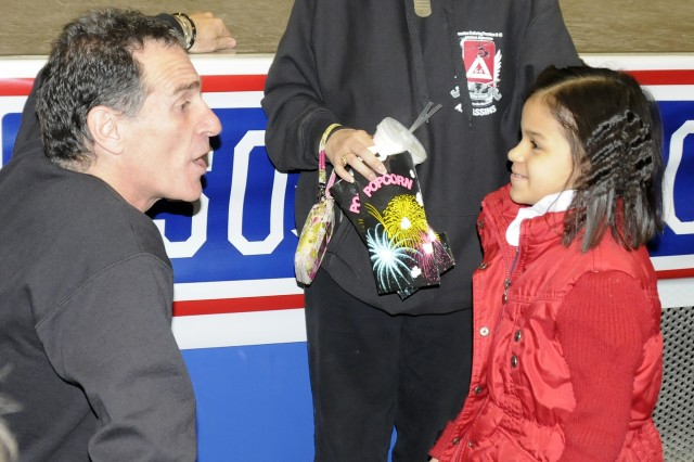 """Jennifer Caprioli Trevor Romain, left, shares a moment with Salisa Wellenreuther, 6, following a """"With You All the Way"""" tour performance at the Multipurpose Auditorium, March 3. The event, hosted by Fort Drum's USO, was designed to teach children in military Families, as well as their friends, how to cope with the stress of all aspects of deployments. Children who attended will recieve a deployment kit, equipped with tools such as a journal, six Trevor Romain DVDs and a book by Romain."""