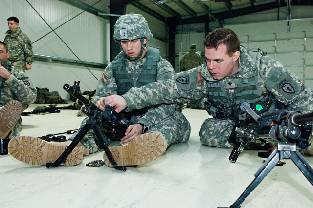 JOINT BASE ELMENDORF-RICHARDSON -- Spc. Jeremy Walker, A Company, 1st Battalion, 501st Infantry Regiment (Airborne), 4th Brigade Combat Team (Airborne), shows a fellow Soldier how to turn the barrel of the M240B machine gun while practicing assembling and disassembling the weapon. Walker is part of a group of Soldiers who were training for their Expert Infantry Badge, Feb. 22.
