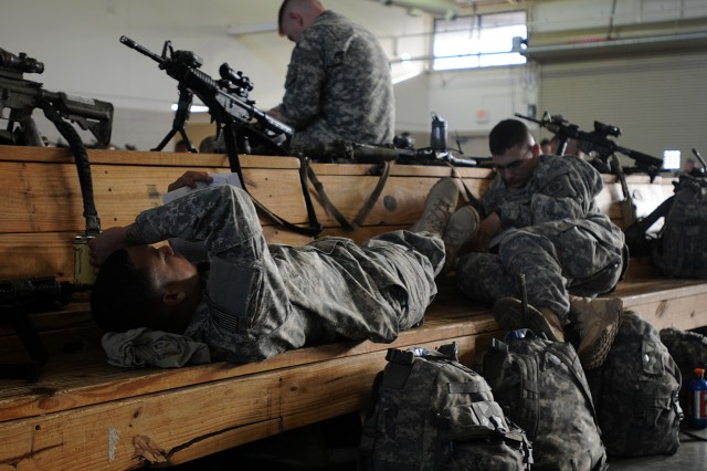 Catching a quick nap, talking on cell phones, reading a book, or listening to music, Paratroopers from the 2nd Brigade Combat Team, 82nd Airborne Division, wait for an aircraft at Pope Army Air Airfield, to take them to a training rotation at the Joint Readiness Training Center in Fort Polk, La., Mar. 8. (U.S. Army photo by Sgt. 1st Class Seth Laughter, 2SFAB PAO NCOIC)