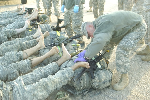 Medical personnel check the feet of Pre-Ranger students immediately following their 14-mile road march during the Pre-Ranger Assessment Course at Fort Irwin, March 1. The course started with almost 40 students on Feb. 28, and ended with only eight graduates.
