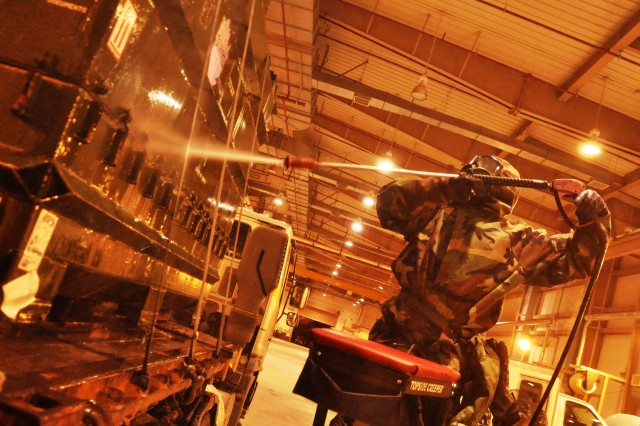 Staff Sgt. James Masterson, a 194th Combat Sustainment Support Battalion Soldier who specializes in protecting service members against chemical, biological, radiological and nuclear threats, sprays a bleach-water mix on cargo containers at Osan Air Base, South Korea on Mar. 10, 2011.  The Roanoke, Va. native was part of a team from the 501st Sustainment Brigade ensuring vehicles were cleaned to prevent the spread of hoof and mouth disease.