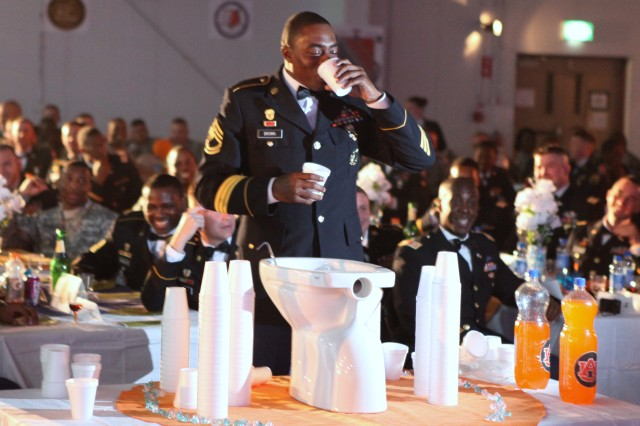 "CAMP ARIFJAN, Kuwait - Sgt. 1st Class Dennis Brown, 228th Signal Company 1st Sergeant, closes his eyes before downing a cup of ""Desert Nectar"" from the grog bowl. Because of theater regulations prohibiting alcohol, carbonated beverages, juices, brown sugar and a dirty sock were used to make the ceremonial drink. The Grog Bowl Ceremony was conducted as part of the 54th Signal Battalion\'s Dining In event, commemorating 20 years of service in SW Asia. (U.S. Army photo by Spc. Jacob Massey, 160th Signal Brigade Public Affairs)"