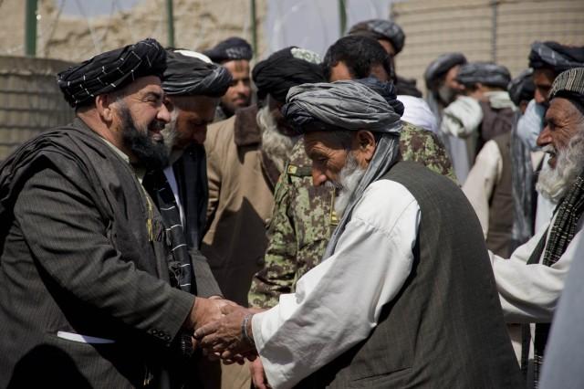 Panjwai district Governor Haji Faizluddin Agha (left) greets district elders before a local shura, Mar. 6, 2011, in Panjwai district, Kandahar province, Afghanistan.