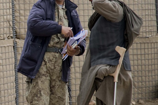 Abdullah, who lost a leg after stepping on an insurgent emplaced improvised explosive device while farming near his home, talks with an Afghan National Civil Order Policeman at a shura March 6, 2011, held in Panjwai district, Kandahar province, Afghanistan.  Abdullah walked the short trip to the shura from his home in order to listen to the Panjwai district Governor Haji Faizluddin Agha, speak to the area elders about how to improve security in the district.