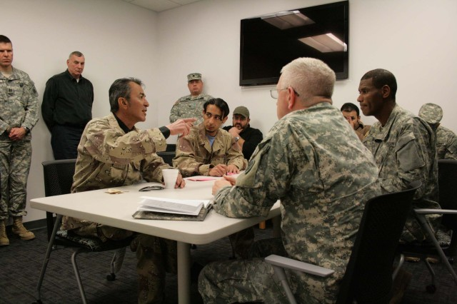 Iraqi role players discuss issues with U.S. Army officers being trained during a Battle Command Training Program (BCTP) exercise. BCTP Observer-Trainers watch from the background.