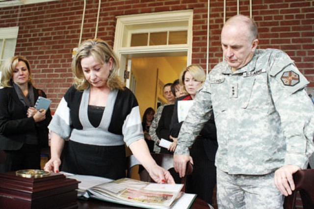 IMCOM Commanding General Lt. Gen. Rick Lynch, and his wife, Sarah, look at a scrapbook created by Jessica Richter, financial adviser, Survivor Outreach Services, during a March 3 visit to the SOS building located in Grimes Hall, Building 510 on Main Post, Fort Riley.