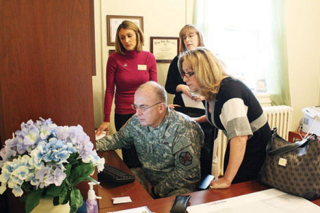 IMCOM Commanding General Lt. Gen. Rick Lynch, foreground left, and his wife, Sarah, foreground right, view the Fort Riley Survivor Outreach Services Facebook page March 3 during a visit to the program's facility, located in Grimes Hall, Building 510 on Main Post, as Christina Gary, SOS coordinator, background left, and Jessica Richter, SOS financial adviser, background right, look on.