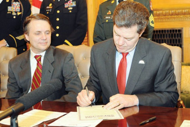 Kansas Gov. Sam Brownback, left, signs the executive order to continue the GovernorAca,!a,,cs Military Council Feb. 24  at the capitol building in Topeka.