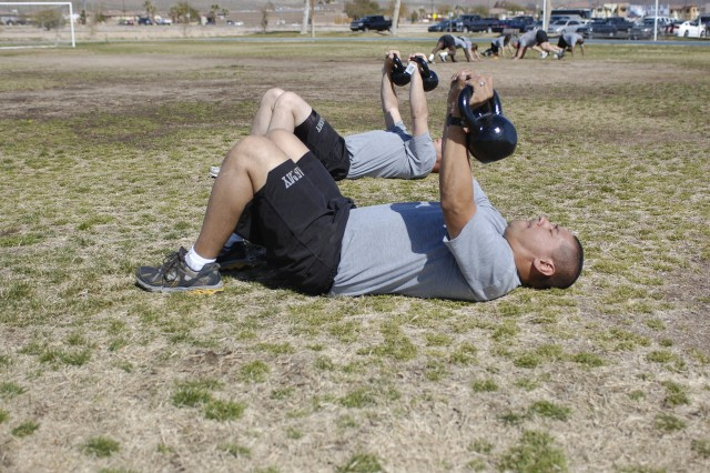 Soldiers stationed at the National Training Center lift kettlebells during a Physical Readiness Training familiarization course at Fort Irwin, Calif., March 10. The exercise is part of the Army's new PRT program, which designed to develop mobility, flexibility and overall strength in the battlefield.