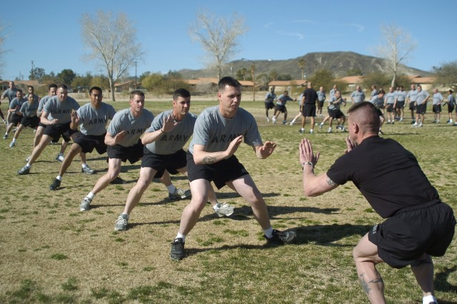 An instructor at the Physical Readiness Training familiarization course demonstrates the proper way to perform lateral movement drills at Fort Irwin, Calif., March 10. A Mobile Training Team from the Army's Physical Fitness School at Fort Jackson, S.C., visited the National Training Center, March 7-10, to train Soldiers on the proper way to conduct PRT sessions.