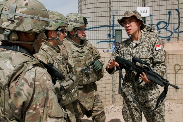 A Singaporean soldier gives an overview of the SAR 21 rifle to a group of U.S. Army Soldiers during a weapons familiarization range Mar. 11, at Multi-National Base Tarin Kot, Afghanistan. The purpose of the range was to give servicemembers from different countries a functional understanding of other nations' weapons.
